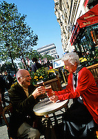 A retired, senior tourist couple toast with beer in an outdoor cafe along Les Champs Elysees. Paris, France.