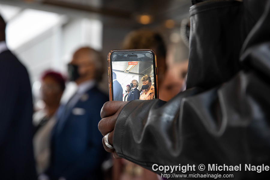 """A smartphone displays Reverend Al Sharpton, center, standing between Lesley McSpadden, mother of Michael Brown, left, and Gwen Carr, mother of Eric Garner, right, during a press conference in response to the George Floyd and Duante Wright cases after the """"Mother's of the Movement"""" panel at the National Action Network (NAN) Virtual Convention 2021 in New York on Wednesday, April 14, 2021. Photograph by Michael Nagle"""