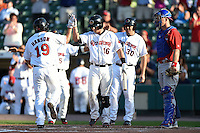Rochester Red Wings designated hitter Nate Hanson (19) high fives Dan Rohlfing (16) after hitting a home run as catcher Erik Kratz (39) looks on during the second game of a doubleheader against the Buffalo Bisons on July 6, 2014 at Frontier Field in Rochester, New  York.  Rochester defeated Buffalo 6-1.  (Mike Janes/Four Seam Images)