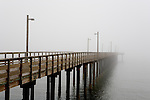 Public fishing pier disappears into fog on Battery Point, where the Pacific Ocean meets Crescent City Marina.   Battery Point was an early hazard to shipping, primarily lumber, from Crescent City, CA.  The lighthouse, lit in 1856, was one of the earliest on the coast.  Crescent City sits along the famous Del Norte Coast of CA.