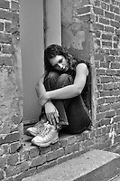 A teenage girl sitting in a window ledge in an alley with her arms wrapped around her knees looking sad or depressed.