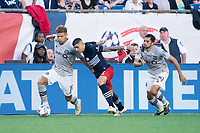 FOXBOROUGH, MA - JULY 25: Gustavo Bou #7 of New England Revolution comes in to tackle Zorhan Bassong #19 of CF Montreal during a game between CF Montreal and New England Revolution at Gillette Stadium on July 25, 2021 in Foxborough, Massachusetts.