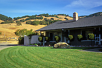 California brown hills with suburban house and green lawn