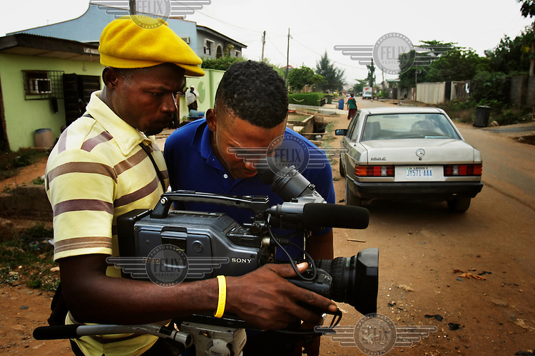 Director Elvis Chucks (right) and a film crew with a video camera on the set of a low-budget Nollywood movie production.