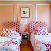 A photograph by Monica Stevenson hangs above a Kartell table lamp in the pink guest bedroom