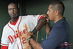 Third baseman Vladimir Frias (29) of the Greenville Drive is worked on in the dugout by trainer David Herrera during a game against the Lakewood BlueClaws on May 13, 2010, at Fluor Field at the West End in Greenville, S.C. Frias was struck on the arm during a play on the field. He remained in the game.