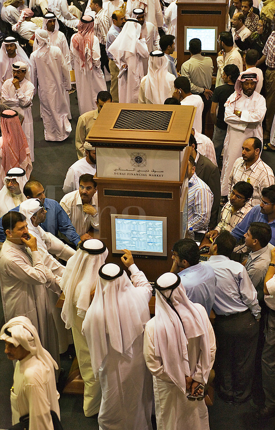 Investors at the Dubai Financial Market, the local Stock Exchange,  concentrate on the display showing the latest prices.  Dubai. United Arab Emirates.
