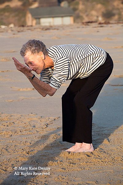 Mature gray haired woman with hands in front of her bends down in move for.exercise dance class on the Playa del Rey Beach in California