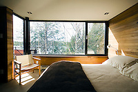 The bedroom is simply furnished with walls lined with cedar wood panelling and huge windows with views over the lake