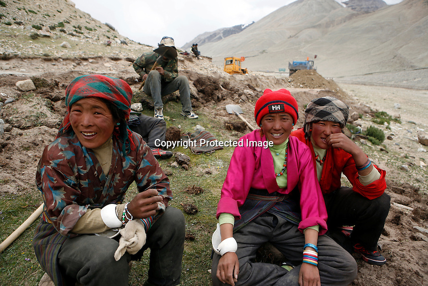 """China started building a controversial 67-mile """"paved highway fenced with undulating guardrails"""" to Mount Qomolangma, known in the west as Mount Everest, to help facilitate next year's Olympic Games torch relay./// Tibetan women take a rest while working on the road to EBC. <br /> Tibet, China<br /> July, 2007"""