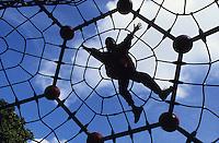 Germany, Hamburg, child at playgrund in Hamburg / DEUTSCHLAND, Hamburg, Junge klettert in einem Netz auf dem Spielplatz