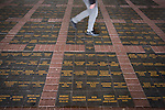 Newcastle United 1 Tottenham Hotspur 3 19/04/2015. St James Park, Premier League. A supporter walking across commemorative plaques in the floor, situated outside the Milburn Stand of the stadium before Newcastle United host Tottenham Hotspurs in an English Premier League match at St. James' Park. The match was boycotted by a section of the home support critical of the role of owner Mike Ashley and sponsorship by a payday loan company. The match was won by Spurs by 3-1, watched by 47,427, the lowest league gate of the season at the stadium. Photo by Colin McPherson.