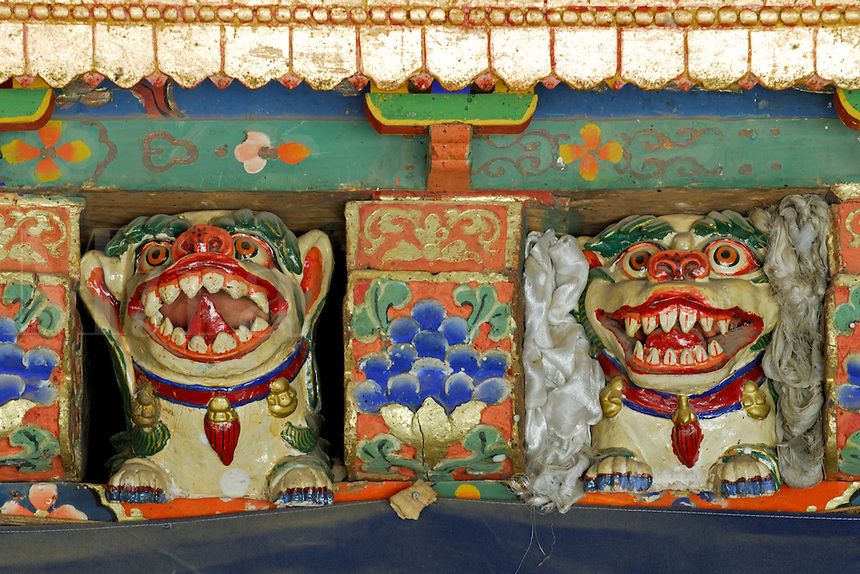 Fierce wood-carved painted animals guard the entrance to Hamdong Kangtsang, residence for monks studying at Sera Je College, Sera Monastery, Lhasa, Tibet, China.