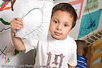 Preschool ages 3-5 proud boy holding up drawing serious horizontal
