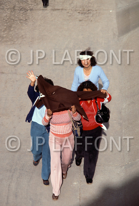 January, 1983. El Paso, Texas. Mexican men and women hide their faces while crossing the Rio Grande River into Texas.