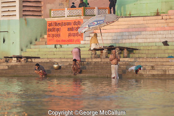 Devotees performing morning Puja in Ganges river Jain Ghat, Varanasi, India