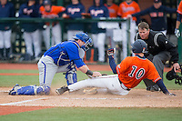 Pavin Smith (10) of the Virginia Cavaliers is tagged out at home plate by Seton Hall Pirates catcher Tyler Boyd (30) as home plate umpire Greg Howard looks on at The Ripken Experience on February 28, 2015 in Myrtle Beach, South Carolina.  The Cavaliers defeated the Pirates 4-1.  (Brian Westerholt/Four Seam Images)