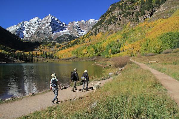 Senior couple hike with dog along Maroon Lake, Maroon Bells, Colorado.
