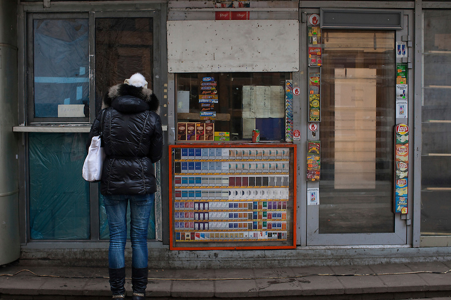 Moscow, Russia, 14/11/2010..A woman stares into an abandoned kiosk with a closed sign near a metro station after new Mayor Sergei Sobyanin ordered the removal of hundreds of the structures, mainly in the city centre. The kiosks, which are ubiquitous throughout the Russian capital, appeared after the fall of the Soviet Union in response to consumer demand and sell a wide range of goods, but most specialise in foodstuffs, alcohol and tobacco.
