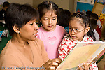 Education preschoool children ages 3-5 female teacher reading picture book to group of girls horizontal