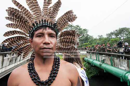 An indigenous leader in a feather headdress stands in front of a line of army troops at a demonstration by indigenous people, the Landless People's Movement (MST) and other civil society groups in front of the Riocentro United Nations conference. The demonstrators are kept out of earshot and invisible to the UN conference. The United Nations Conference on Sustainable Development (Rio+20), Rio de Janeiro, Brazil, 20th June 2012. Photo © Sue Cunningham.