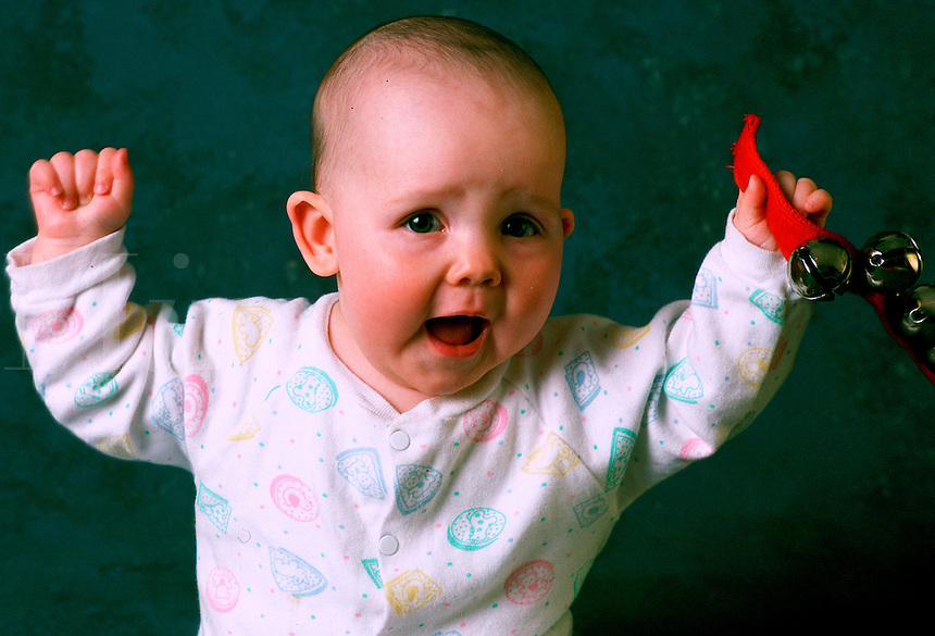 Infant girl vocalizes and shakes her bell toy.