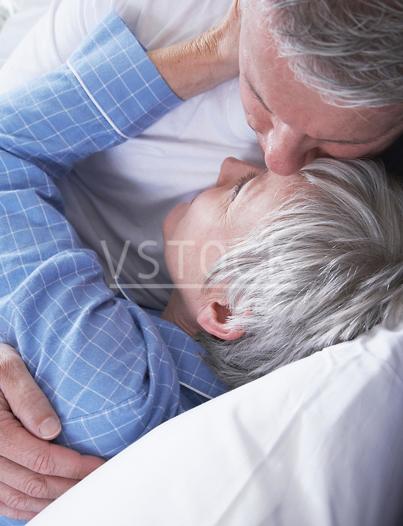 Mature couple embracing in bed