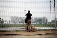 """CHINA. Beijing. A man looks through a fence, trying to catch a glimpse of the new Olympic park. In recent years construction has boomed in Beijing as a result of the country's widespread economic growth and the awarding of the 2008 Summer Olympics to the city. For Beijing's residents however, it seems as their city is continually under construction with old neighborhoods regularly being razed and new apartments, office blocks and sports venues appearing in their place. A new Beijing has been promised to the people to act as a showcase to the world for the 'new' China. Beijing's residents have been waiting for this promised change for years and are still waiting, asking the question """"Where's the new Beijing?!"""". 2008."""