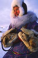 Portrait of a smiling Alaskan woman in heavy fur coat, hood and mittens. Alaska.