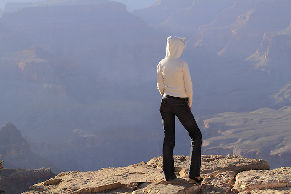 Thin, young woman standing on the edge of the South Rim of Grand Canyon National Park, northern Arizona, USA . John offers private photo tours in Grand Canyon National Park and throughout Arizona, Utah and Colorado. Year-round.