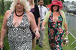 Working class women, overweight, showing cleavage wearing summer dresses. Ladies Day at the Derby horse race. Epsom Down Surrey UK. 2012