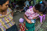 The wives of mahouts at Thayatsan elephant  camp express their breast  milk to provide food for  the orphaned and weakened elephant calf Mi Chaw who was abandoned by her mother.  The calf has been suffering from severe diarrhoea caused by the cheap artificial milk-powders previously fed to her by the villagers. <br />
