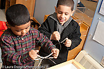 Education preschool 3-4 year olds two boys in kitchen area playing with tongs horizontal