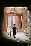 Play is where you find it.  A boy roles a bicycle tire down a narrow walkway in a Moroccan village.