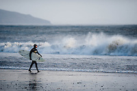 Friday 03 January 2014<br /> Pictured: A surfer walks along Saundersfoot Beach, West Wales with waves crashing behind him<br /> Re: Storm force winds and some of the highest tides in decades hit Wales early on Friday.