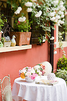 A multi coloured selection of freshly cut roses on a garden table covered with a crisp white tablecloth