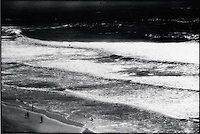 People walking along seashore<br />
