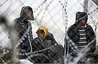Pictured: Refugees as seen through the barbed-wire fence Monday 29 February 2016<br /> Re: A crowd of migrants has burst through a barbed-wire fence on the FYRO Macedonia-Greece border using a steel pole as a battering ram.<br /> TV footage showed migrants pushing against the fence at Idomeni, ripping away barbed wire, as FYRO Macedonian police let off tear gas to force them away.<br /> A section of fence was smashed open with the battering ram. It is not clear how many migrants got through.<br /> Many of those trying to reach northern Europe are Syrian and Iraqi refugees.<br /> About 6,500 people are stuck on the Greek side of the border, as FYRO Macedonia is letting very few in. Many have been camping in squalid conditions for a week or more, with little food or medical help.