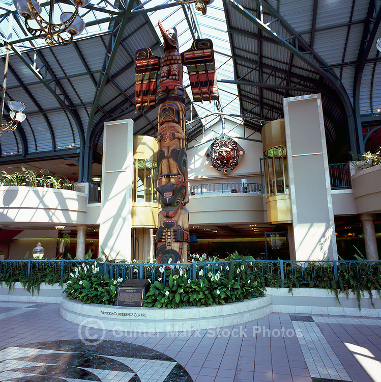 "Victoria Conference Centre Lobby, Victoria, BC, Vancouver Island, British Columbia, Canada - Interior with Kwakwaka'wakw (Kwakiutl) Totem Pole (carver Tony Hunt - 1989 - Raven on Top, Sisiutl below, and Grizzly Bear holding Halibut on Bottom) and  ""Whale People Spindlewhorl"" (artist Susan Point - 1999) on upper back wall"