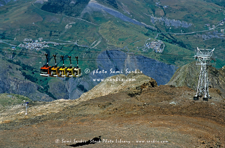 Overhead cable car travelling up the mountainous landscape of La Meije, French Alps, France.