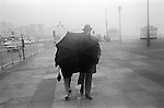 Middle aged couple walking during traditional English seaside bad weather Brighton sea front promenade. Sussex England 1969. 1960s UK