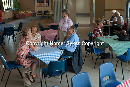 St Walstans Day, Bawburgh, Norfolk 2018. Village Hall, Revd Penny Goodman  and members of the community gather for a Ploughmans lunch and home made cakes after the procession to St Walstans healing holy well.