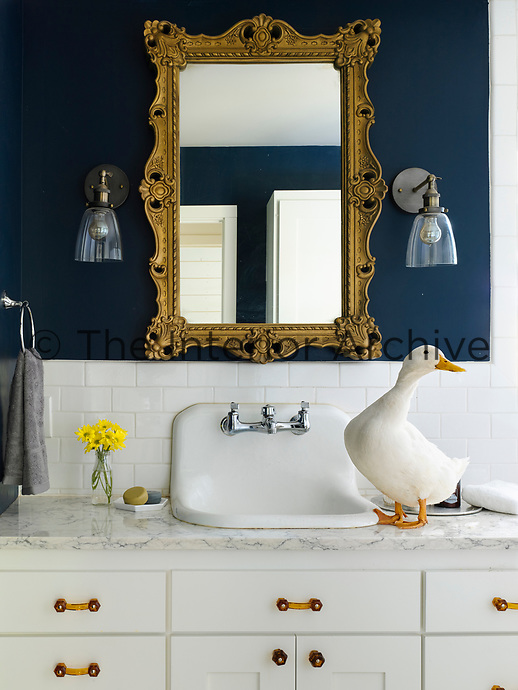 The bathroom is painted in royal navy blue by Valspar. Wall lights hang either side of an antique gilt mirror. The wash basin is set in a marble top with storage below.