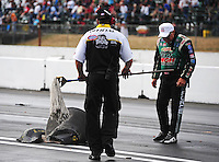 Aug. 5, 2011; Kent, WA, USA; NHRA funny car driver John Force examine the blown tire from the car of teammate Robert Hight (not pictured) after it exploded during qualifying for the Northwest Nationals at Pacific Raceways. Mandatory Credit: Mark J. Rebilas-