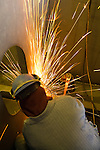 Welders welding various parts for barge assembly