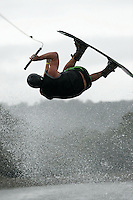 A male wakeboard competitor flips upside down during her tricks run during a competition.