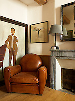 A large framed portrait rests on the floor beside a leather armchair in the living room