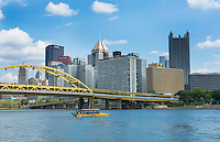 Pittsburgh Pennsylvania PA downtown skyline skyscrapers with famous Just Ducky Tours boat going around city and Roberto Clemente Bridge