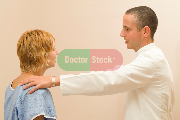 doctor or similar places reassuring hand on female patients shoulder