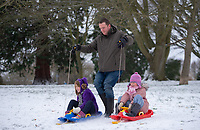 Dad pulls his daughters while sledging in the park in Sidcup following Heavy Snowfall at Sidcup, Kent, England on the 8 February 2021. Photo by Alan Stanford.